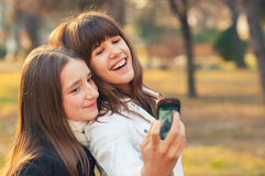 Two teenage girls taking selfies in the park on sunny autumn day Royalty Free Stock Photo