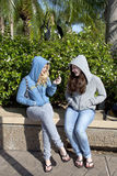 Two Teenage Girls Talking, a Boy Left Out. Two teenage girls, white, sitting and talking to each other.  Both are smiling and sitting similarly.  Both are Royalty Free Stock Image