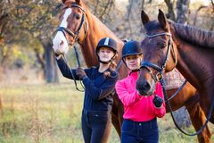 Two teenage girls with their horse in park Royalty Free Stock Photography
