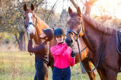 Two teenage girls with their horse in park Royalty Free Stock Photo