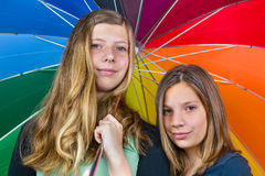 Two teenage girls under colorful umbrella Royalty Free Stock Photo