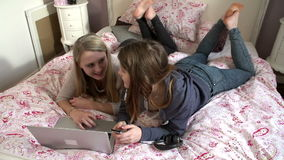 Two Teenage Girls Using Digital Devices In Bedroom. Two teenage girls relaxing in bedroom - one using laptop whilst the other sends text message.Shot on Sony stock footage