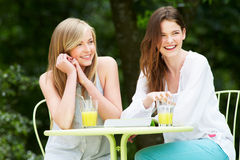 Two Teenage Girls Using Digital Tablet In Outdoor cafe Stock Images