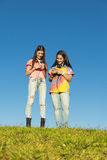 Two Teenage Girls Using Mobile In Park Stock Images