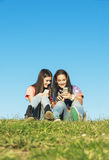 Two Teenage Girls Using Mobile In Park Stock Image