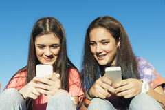 Two Teenage Girls Using Mobile In Park Royalty Free Stock Photos