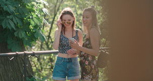 Two teenage girls using mobile phone in a city park. Beautiful young women watching photos on a phone stock footage