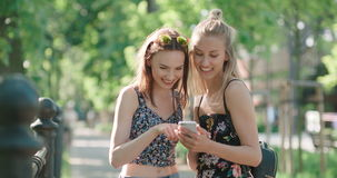 Two teenage girls using mobile phone in a city park. Beautiful young women watching photos on a phone stock video