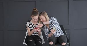 Two teenage girls using mobile phones. Happy teenage girls discussing while using mobile phones stock footage