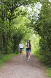 Two teenage girls walking down a country lane Stock Photography