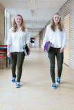 Two teenage girls walking in long school corridor carrying text books Stock Image