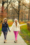 Two teenage girls walking in the park Royalty Free Stock Images