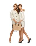 Two teenage girls in white coats with bag Royalty Free Stock Photo