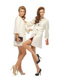 Two teenage girls in white coats with clutches Stock Photography