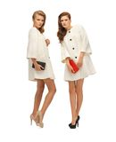 Two teenage girls in white coats with clutches Stock Image