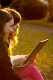 Two teenage girls working on notebook in the park. Two beautiful teenage girls having fun with notebook in the park on sunny spring day Stock Image