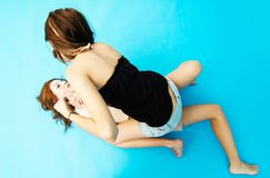 Two Teenage Girls Wrestling 2. Two teenage girls wrestling on the floor.  One girl is sitting on top of the other Royalty Free Stock Photography