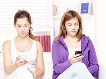 Two teenage girs with mobile phones Stock Photography