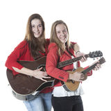 Two teenage sisters play ukelele and guitar in studio Royalty Free Stock Images