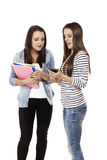Two teenage students looking at a smartphone Stock Images