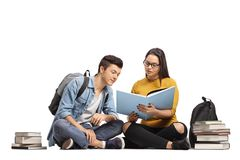 Two teenage students sitting on the floor and studying. Isolated on white background Stock Photo