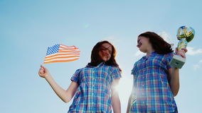 Two teenage twins girls with a winner`s cup and an American flag. Champions in sport, victories, achievements stock footage