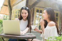 Two teenage women meet in coffee shop use laptop together in aft stock photos