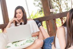 Two teenage women sit on big hammock use laptop together in afternoon stock images