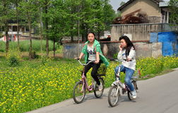 Pengzhou, Chin: Teenaged Girls Bicycling. Two teenaged Chinese girls riding their bicycles along a country road pass a field of yellow Rapeseed oil flowers in Stock Images