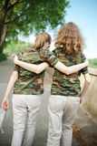 Two teenaged friends in camouflage t shirts royalty free illustration