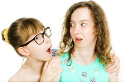 Two teenaged sisters posing together - looking at each other in royalty free stock image