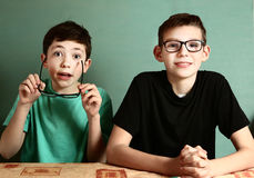 Two teenager boys in myopia glasses close up. Portrait on blue wall background stock photography