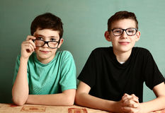 Two teenager boys in myopia glasses close up. Portrait on blue wall background stock images