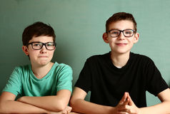 Two teenager boys in myopia glasses close up. Portrait on blue wall background royalty free stock photography