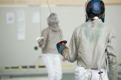 Two teenager fencers in white protective clothes fighting on the fencing tournament. Rear view shot royalty free stock photos