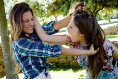 Two teenager friends fighting in park angry pulling long hair shouting Stock Image