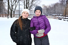 Two teenager girl on the snowy white background Royalty Free Stock Image