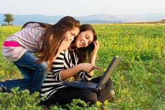 Two teenager girls with laptop computer in nature. Two teenager girls with laptop computer surfing internet in nature royalty free stock photography