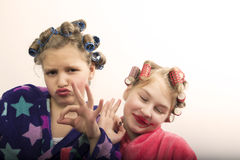 Two teenager girls playing Housewives, do yourself hairstyles and makeup having fun.  Stock Photo