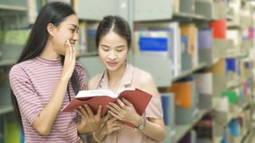 Two teenager girls read a book at book shelf in background . royalty free stock photos
