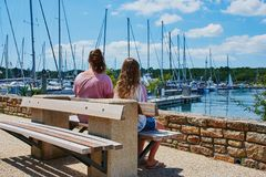 Two teenager girls are sitting at Benodet harbor stock photography
