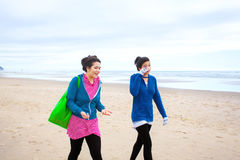 Two teenager girls walking on beach on cool cloudy day Royalty Free Stock Photography