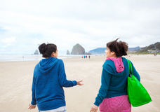 Two teenager girls walking on beach on cool cloudy day Stock Photography