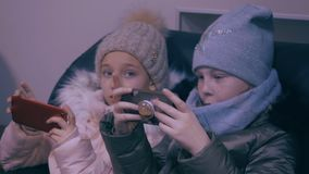 Two teenager girls in winter clothes watching mobile phones and playing in game. Two young girls teenager in winter clothes sits, watching mobile phones and stock footage