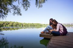 Two teenage girls. Two teenager smiling girls with backpacks sitting on a pier at the river bank and look at laptop, the city in the background Royalty Free Stock Images
