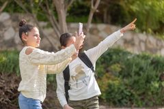 Young girls take a photo with smartphone outdoor. Two teenager travel bloggers are trying to take a photo in unfamiliar city. Young girl is holding smartphone stock photo