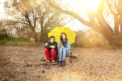 Two teenager with umbrella sitting on a dirty beach. With sun in background Stock Photography