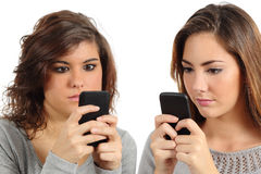 Two teenagers addicted to the smart phone technology. Isolated on a white background stock image