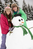 Two Teenagers Building Snowman On Ski Holiday Stock Photos
