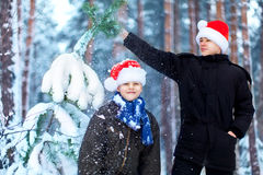 Two teenagers in Christmas hats Santa Claus having fun in the sn Royalty Free Stock Photography